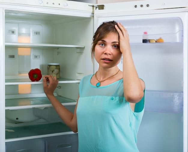 Ragazza affamata vicino al frigo vuoto
