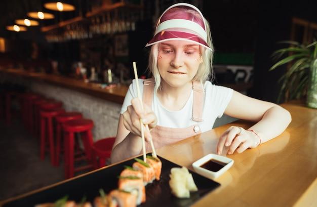 Una ragazza affamata con le bacchette in mano prende un rotolo di sushi dal suo piatto