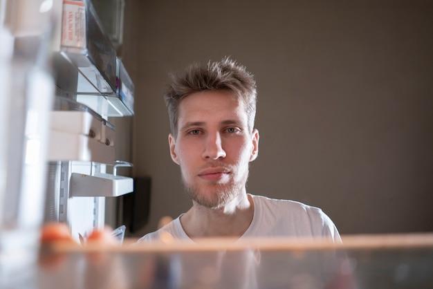 Uomo affamato che cerca uno spuntino in frigo di notte, vista dai frigoriferi