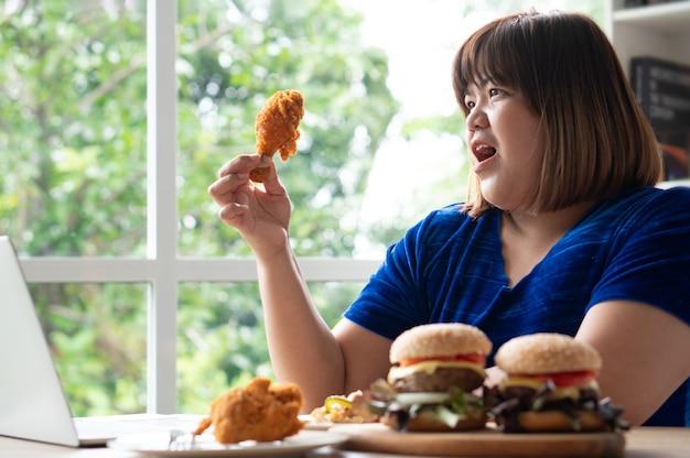 Donna sovrappeso affamata che tiene pollo fritto, hamburger su un piatto di legno e pizza sul tavolo, durante il lavoro da casa, aumenta il problema di peso. concetto di disturbo da alimentazione incontrollata (bed).