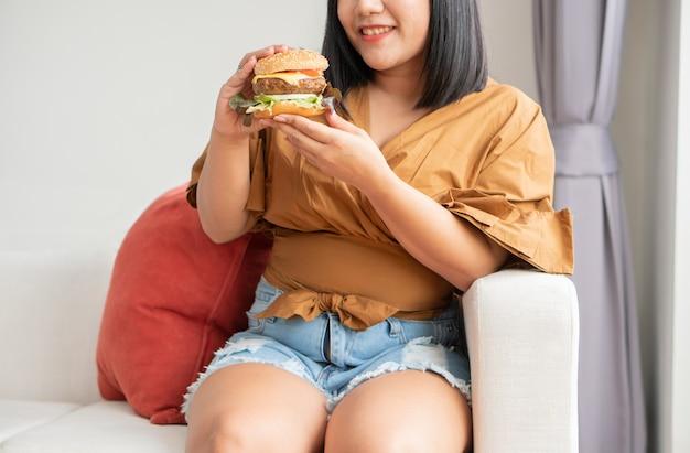 Donna sovrappeso affamata che sorride e che tiene hamburger, è molto felice e si diverte a mangiare fast food