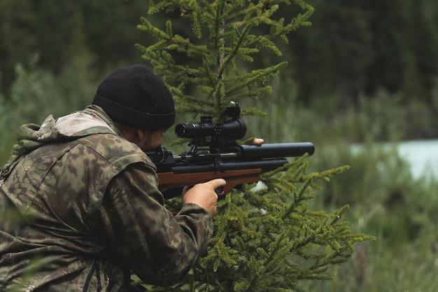 Il cacciatore mira con un fucile. un uomo in mimetica si prepara a sparare. a caccia nel bosco con un fucile da cecchino