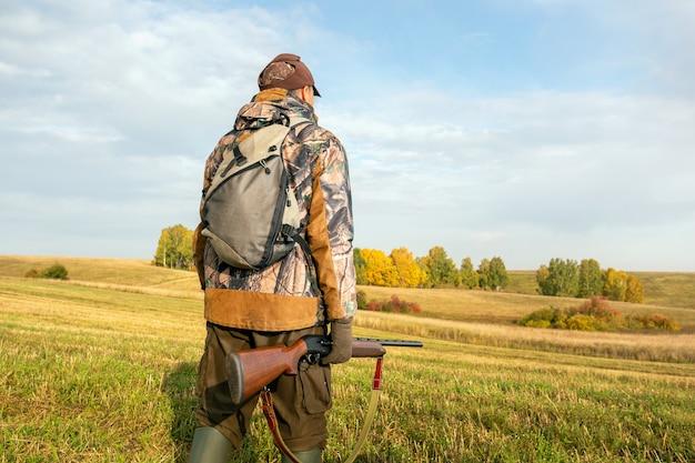 Cacciatore sullo sfondo che cammina sul campo. cacciatore con uno zaino e un fucile da caccia nella stagione autunnale.
