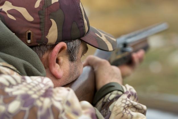 Un cacciatore in mimetica al poligono di tiro calibra l'arma. un uomo spara ai bersagli.