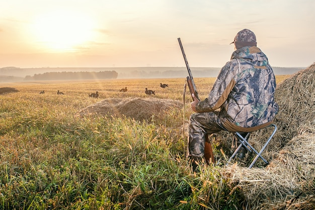 Cacciatore in mimetica con una pistola da caccia su fagiano di monte