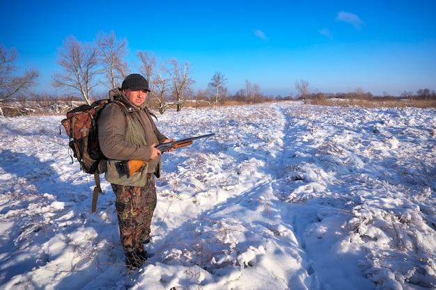 Cacciatore sul campo in attesa della vittima. caccia invernale. hunter completamente preparato.