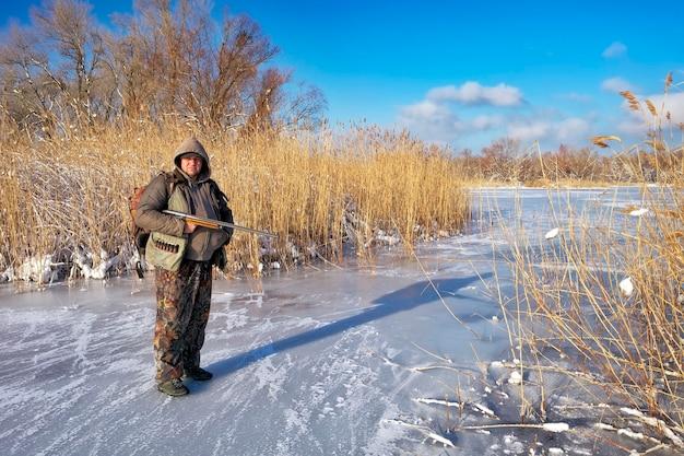Cacciatore sulla vittima in attesa dello stagno ghiacciato. hunter completamente preparato. caccia invernale.