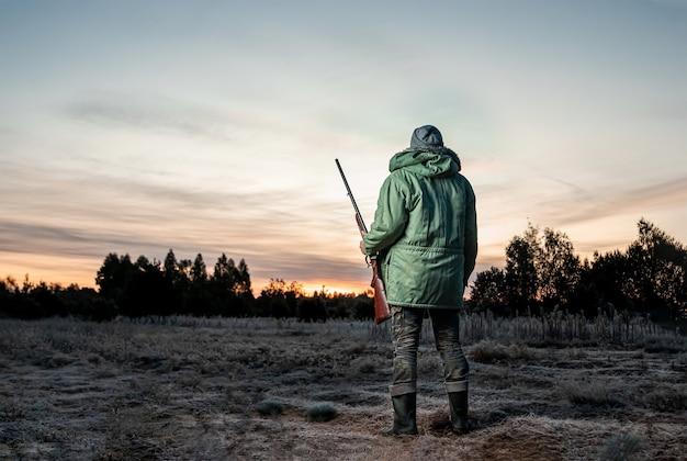 Uomo cacciatore in mimetica con una pistola durante la caccia