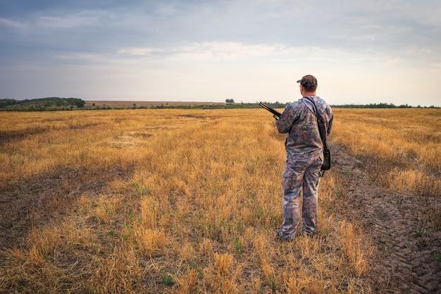 Cacciatore in movimento con fucile in cerca di prede.