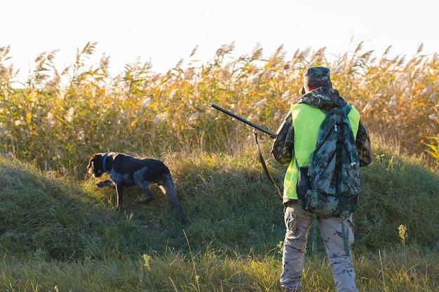 Un cacciatore con una pistola in mano in abiti da caccia nella foresta autunnale in cerca di un trofeo
