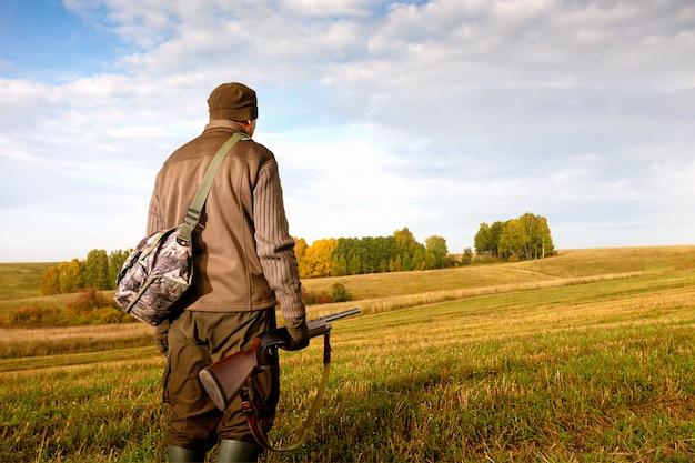 Cacciatore con una pistola a caccia nella stagione autunnale.