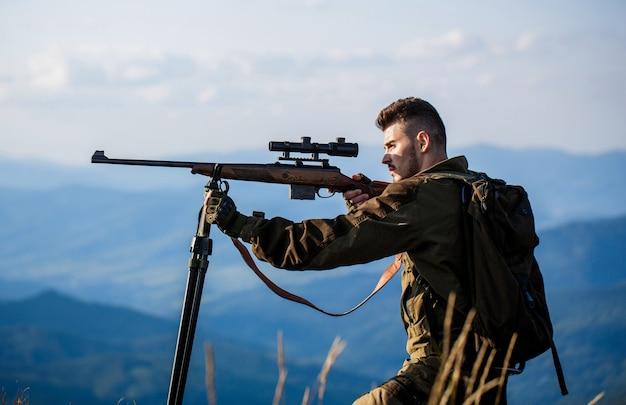 Cacciatore con fucile da caccia e forma di caccia per cacciare. hunter sta mirando.