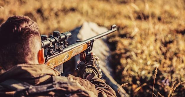 Cacciatore con fucile da caccia e forma da caccia per cacciare. il cacciatore sta mirando.