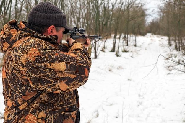 Cacciatore con un fucile da cecchino nella foresta invernale.
