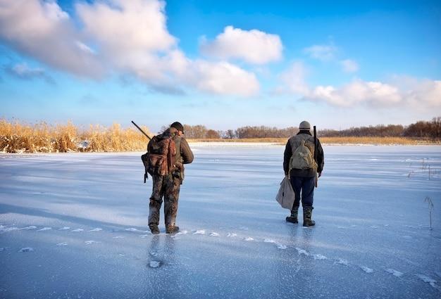 Cacciatori sulla vittima in attesa dello stagno di ghiaccio. caccia invernale.