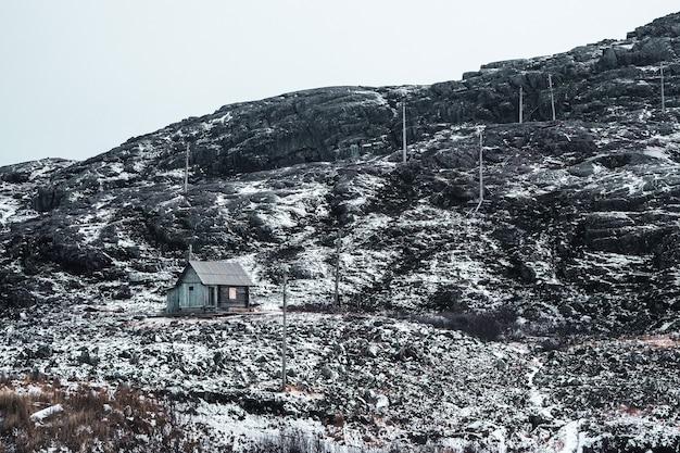 Capanno abbandonato di caccia su una collina artica innevata. vecchio villaggio autentico di teriberka. penisola di kola. russia.
