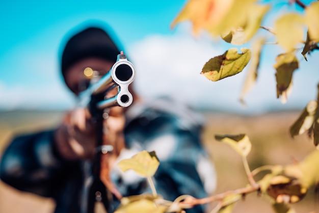 Licenze di caccia. cacciatore con fucile da caccia a caccia. stagione di caccia autunnale. bracconiere con il fucile che individua alcuni cervi. rintracciare.