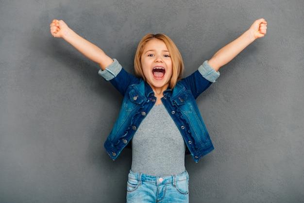 Evviva! bambina allegra che tiene le braccia tese e guarda la telecamera mentre si trova in piedi su uno sfondo grigio