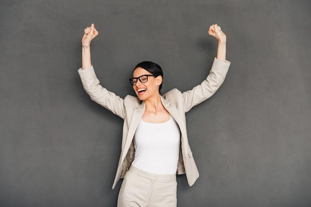 Evviva! allegra giovane donna d'affari con gli occhiali che gesticola e tiene la bocca aperta mentre sta in piedi su uno sfondo grigio