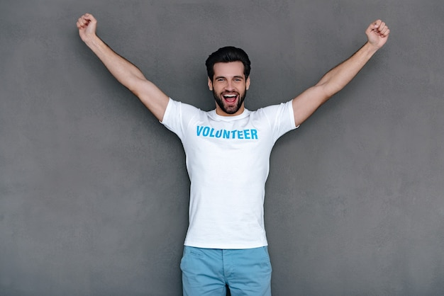 Evviva! giovane allegro in maglietta volontaria che allunga le braccia e guarda la telecamera con un sorriso mentre si trova in piedi su uno sfondo grigio