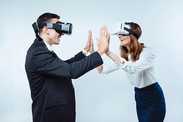 Evviva. amici radiosi che celebrano la loro vittoria dopo aver giocato a giochi di realtà visiva mentre cercano di rilassarsi dopo una dura giornata in ufficio.