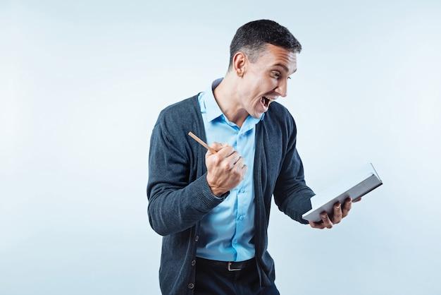 Evviva. un uomo molto felice non può smentire i suoi occhi mentre guarda una pagina del suo taccuino e celebra alcune buone notizie sullo sfondo.