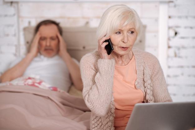 Sbrigati. senior donna che chiama emergenza mentre è seduto sul letto tenendo il computer portatile vicino al marito malato con un terribile mal di testa.