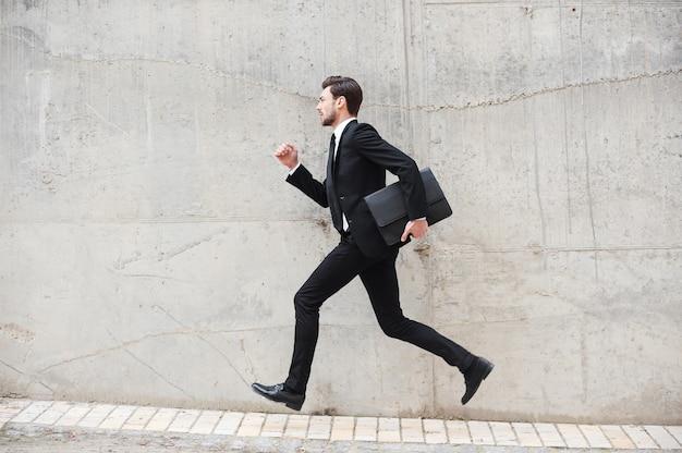 Affrettandosi verso i nuovi obiettivi. felice giovane uomo in abiti da cerimonia che tiene la valigetta mentre corre davanti al muro di cemento concrete
