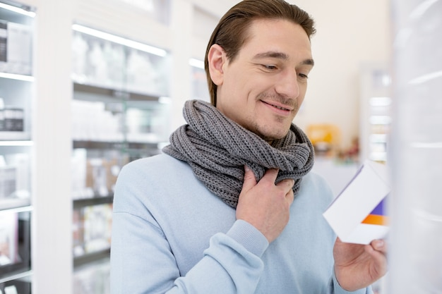 Ferito durante la deglutizione. bell'uomo soddisfatto che indossa una sciarpa mentre si sceglie il farmaco per alleviare i sintomi del raffreddore