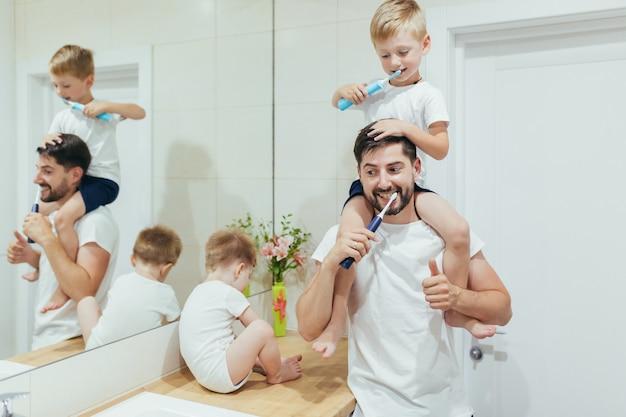 Marito papà insegna al figlio a lavarsi i denti