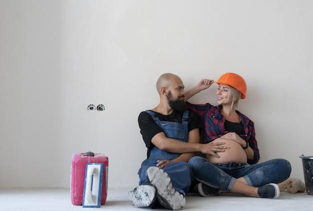 Il marito e la moglie incinta sono seduti per terra nella stanza. uniforme da lavoro e casco di sicurezza arancione. accarezzandosi lo stomaco e guardandosi l'un l'altro. una famiglia felice.