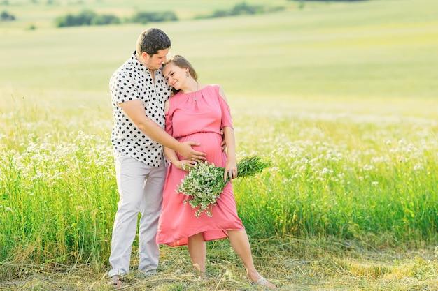 Il marito abbraccia la moglie da dietro e insieme si toccano la pancia. famiglia su sfondo di erba alta e fiori.