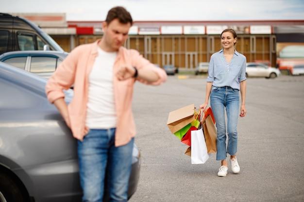 Il marito sta aspettando sua moglie nel parcheggio del supermercato. clienti felici con acquisti vicino al centro commerciale, veicoli, coppia di famiglia nel mercato