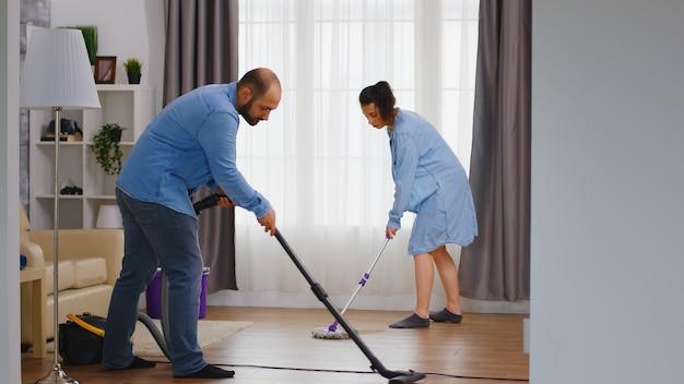 Marito e moglie puliscono la casa insieme usando l'aspirapolvere e il mocio