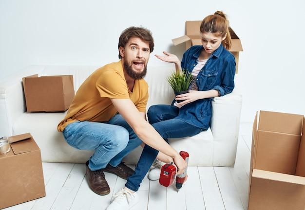 Marito moglie sul divano in un nuovo appartamento scatole con cose in movimento