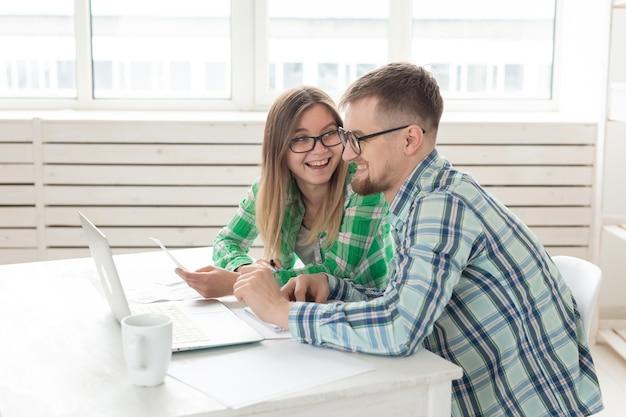 Marito e moglie contano gli acquisti e le bollette dell'ultimo mese e registrano i risultati nella contabilità domestica su un taccuino e su un laptop. concetto di risparmio e contabilità