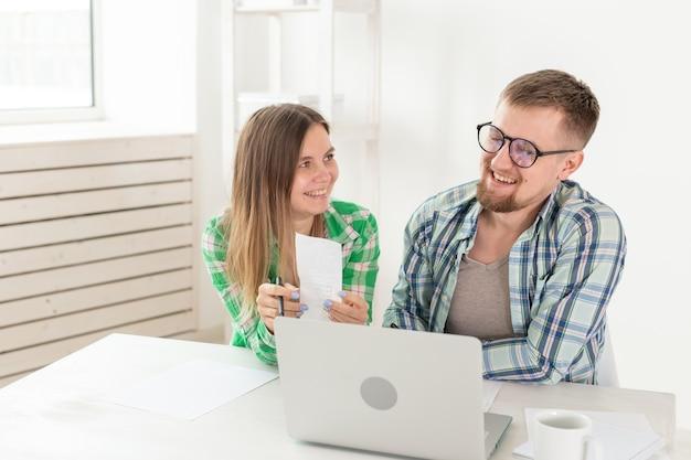 Marito e moglie discutono l'importo dell'assegno per il pagamento dell'appartamento e lo confrontano con le tariffe sul sito ufficiale mentre si è seduti al tavolo con il laptop. concetto di pagamento delle bollette.