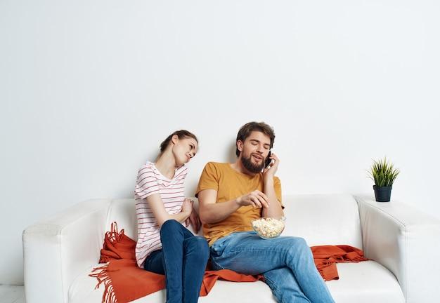 Marito e moglie si divertono a casa sul divano a guardare i popcorn dei film