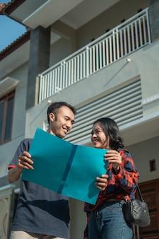 Marito e moglie in possesso di un certificato fondiario con una nuova casa alle spalle