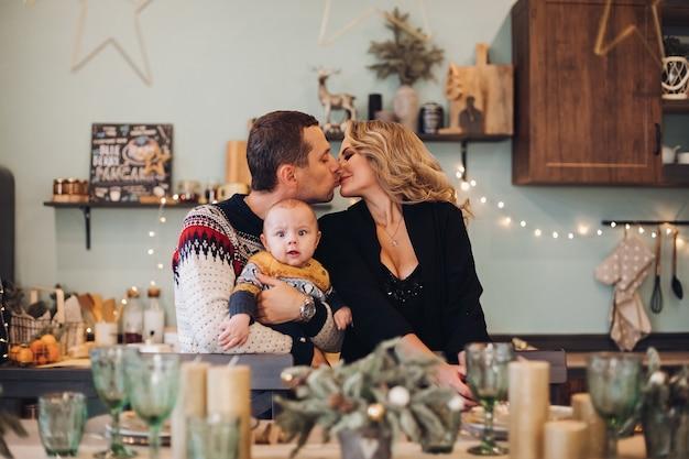 Marito e moglie si baciano mentre tengono un bambino carino e seduti a una tavola festiva di natale. concetto di vacanza