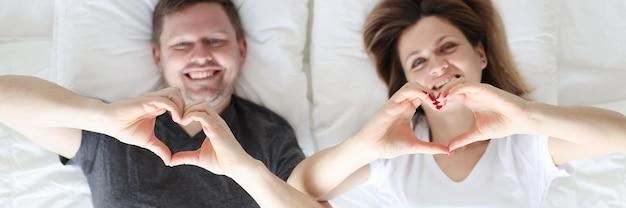 Marito e moglie sdraiati a letto e mostrando i cuori con le mani vista dall'alto matrimonio felice
