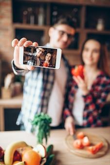 Marito e moglie fanno selfie in cucina. rapporto di coppia felice, famiglia prima di cucinare insalata di verdure