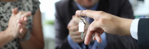 Marito e moglie ricevono la chiave dell'appartamento dal venditore in primo piano dell'ufficio. concetto di prestito di costruzione domestica.