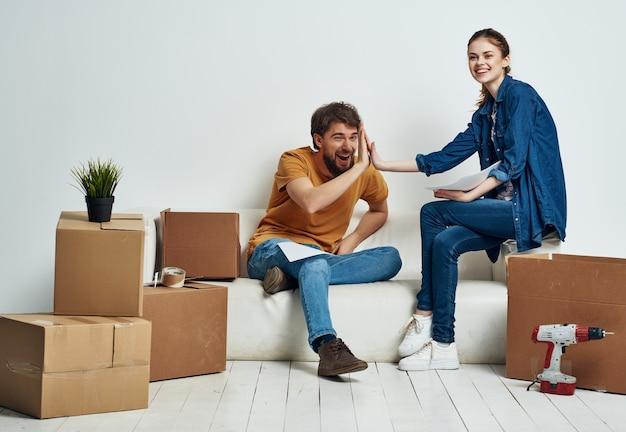 Marito e moglie disfano le scatole in un nuovo appartamento in movimento