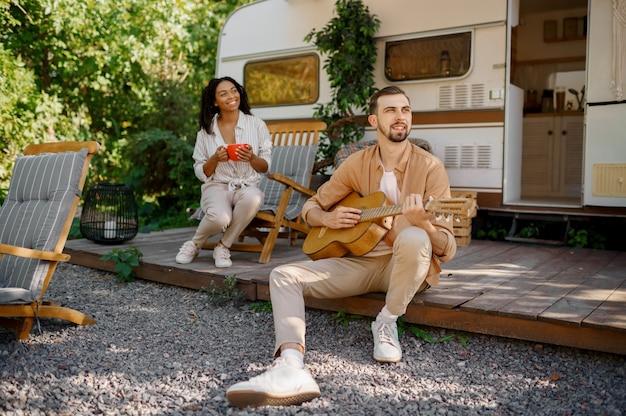Marito con chitarra vicino a camper, avventura su ruote, campeggio in un rimorchio. uomo e donna viaggiano in furgone, vacanze in camper, svaghi campeggiatori in camper