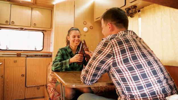 Marito fa ridere sua moglie mentre tiene in mano una bottiglia di birra all'interno del loro camper retrò.