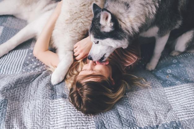 Cucciolo di husky che lecca il volto del suo proprietario femminile.