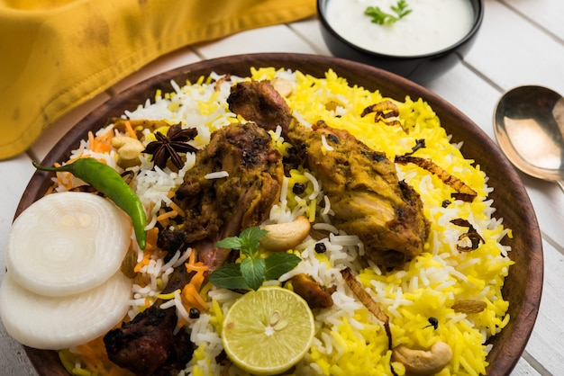 Pollo hyderabadi o dum biryani, servito in un kadhai o in una ciotola con salsa allo yogurt. messa a fuoco selettiva
