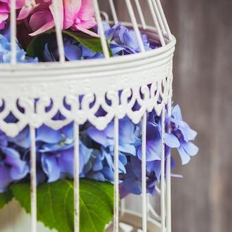 Fiori di ortensia nella gabbia per uccelli bianca. decorazioni floreali per la casa