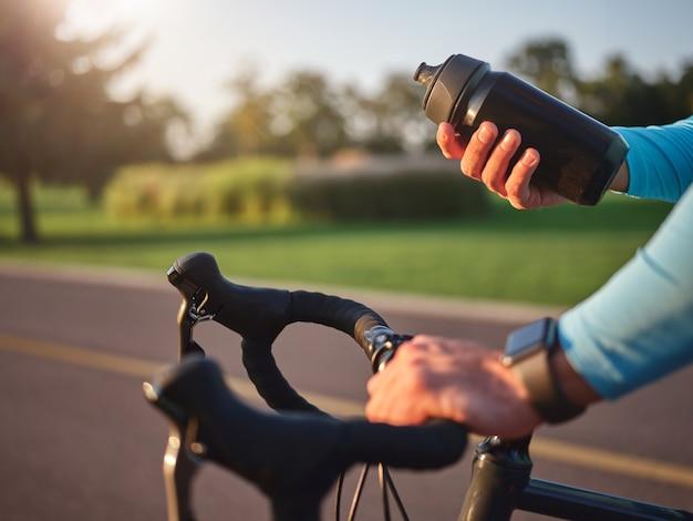 Idrata il tuo corpo vicino alle mani del ciclista professionista che tiene la bottiglia d'acqua in piedi con